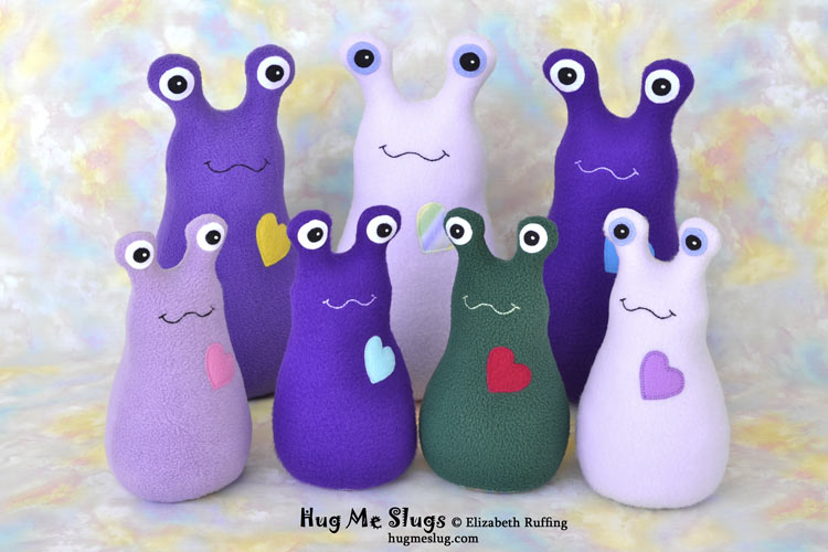 Purple, lavender, and green Hug Me Slugs stuffed animal art toys by Elizabeth Ruffing