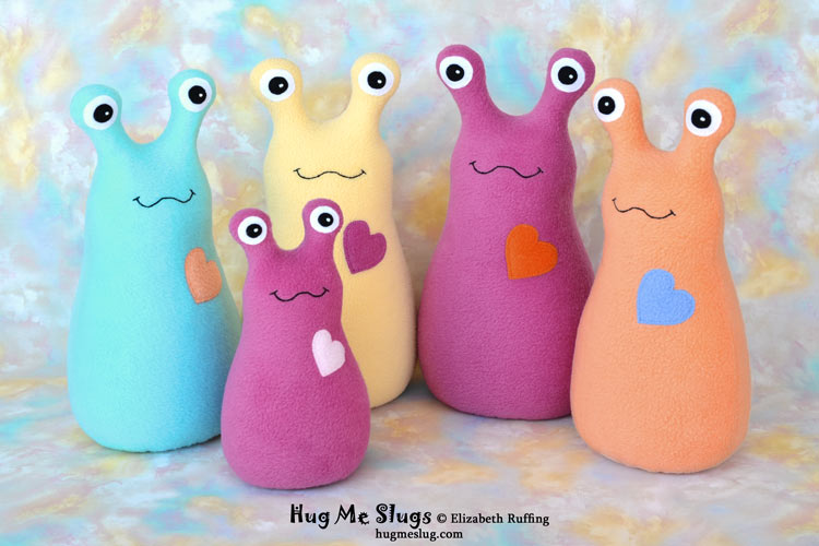 Magenta, turquoise, yellow, orange Hug Me Slugs stuffed animal art toys by Elizabeth Ruffing