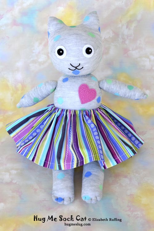 Gray polka dotted Hug Me Sock Cat stuffed animal art toy with a striped skirt by Elizabeth Ruffing
