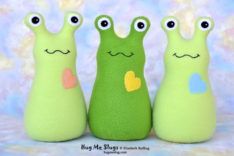 Green fleece Hug Me Slug handmade stuffed animal art toys by artist Elizabeth Ruffing with personalized hang tags