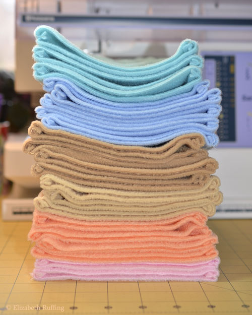 Stack of pastel fleece for Hug Me Bunny stuffed animal art toys by artist Elizabeth Ruffing