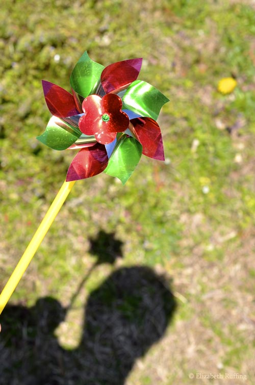 Red and green pinwheel with shadow on the ground, Elizabeth Ruffing