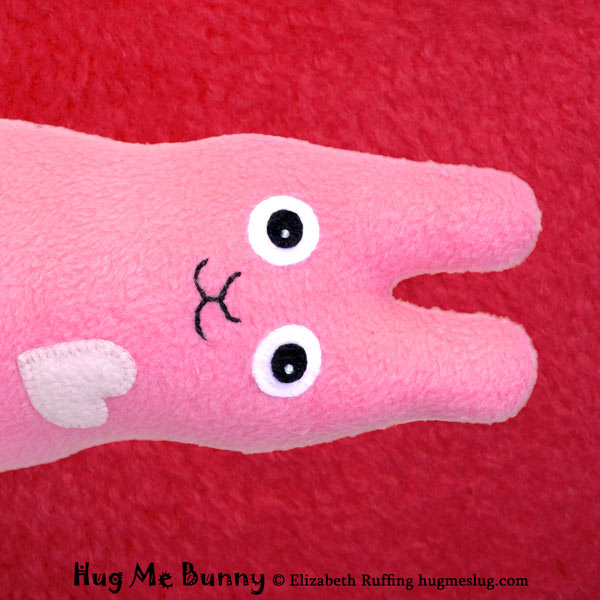 Hug Me Bunny equality symbol, pink fleece rabbit stuffed animal toy on a red background by artist Elizabeth Ruffing