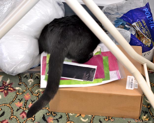 Jojo, black-and-white tuxedo cat with her bottom sticking out from a pile of craft supplies, in artist Elizabeth Ruffing's workroom