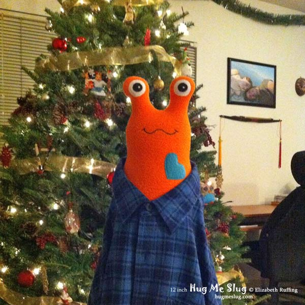 Orange and teal 12 inch Hug Me Slug, plush stuffed animal toys by Elizabeth Ruffing, with Christmas tree