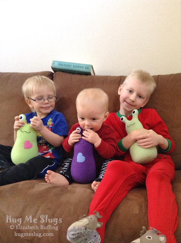Hug Me Slugs, plush stuffed animal art toys hugged by three brothers by Elizabeth Ruffing