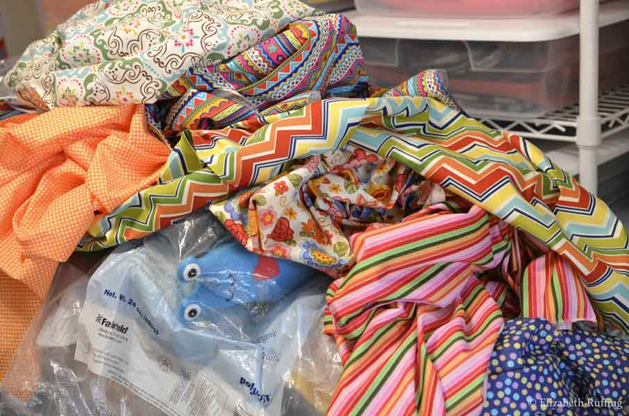 Piles of quilting fabrics with a Hug Me Slug peeking out by Elizabeth Ruffing