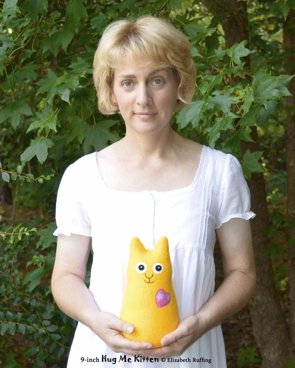 Hug Me Kitten plush art toy, yellow, made and held by Elizabeth Ruffing