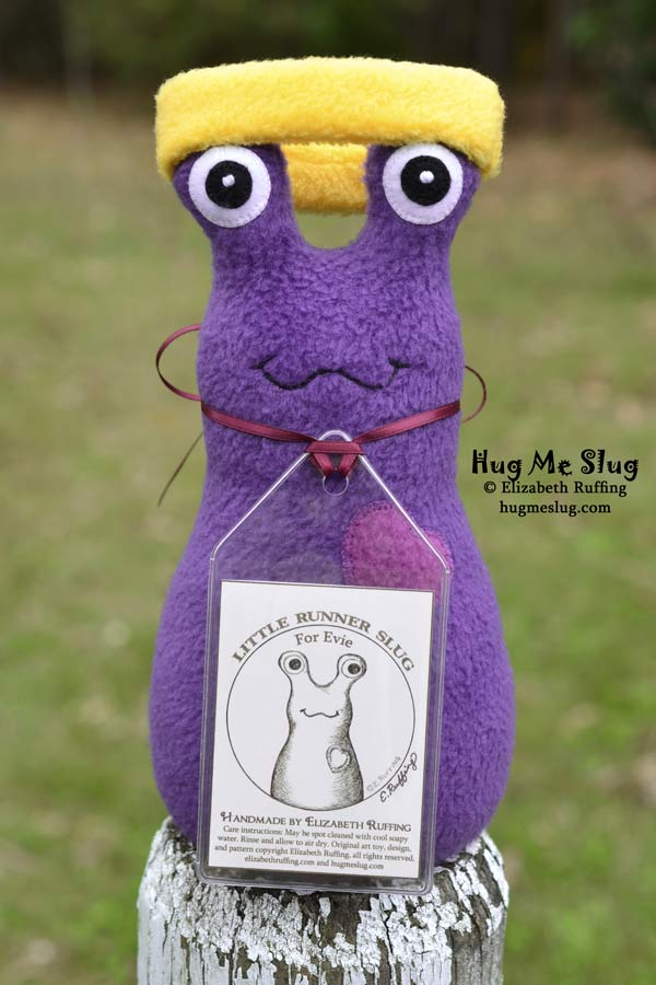 Purple fleece Hug Me Slug stuffed animal art toy with a headband by Elizabeth Ruffing