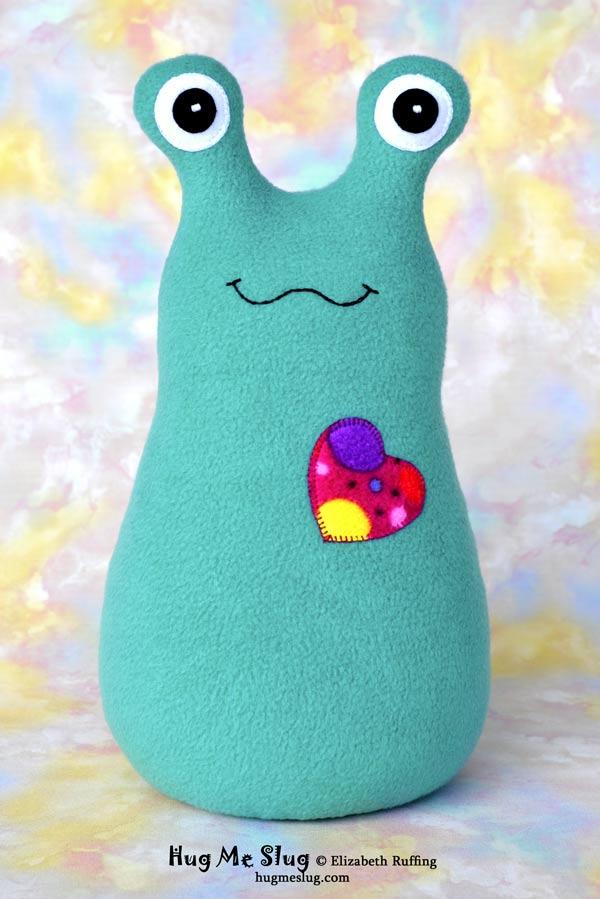 Teal fleece Hug Me Slug stuffed animal art toy with a polka-dotted heart by Elizabeth Ruffing