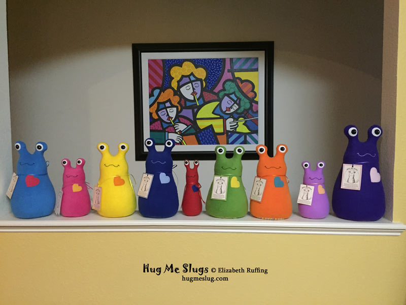 Stuffed toy Hug Me Slugs, assorted colors in a row by Elizabeth Ruffing