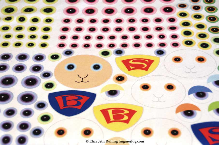 Custom fabric printed superhero emblems, eyeballs, and animal faces on fleece by Elizabeth Ruffing