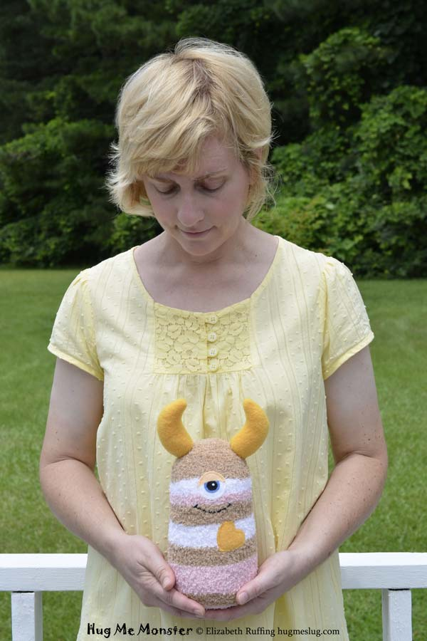 Hug Me Monster, sock doll art toy, pink and tan striped made and held by Elizabeth Ruffing