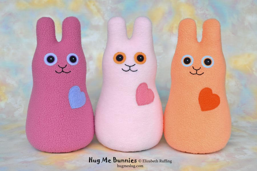 Hug Me Bunnies plush art toys, mauve, pink, and soft orange, by Elizabeth Ruffing