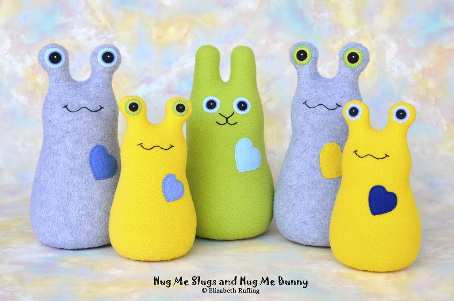 Yellow and gray Hug Me Slugs, apple green Hug Me Bunny plush toys by Elizabeth Ruffing