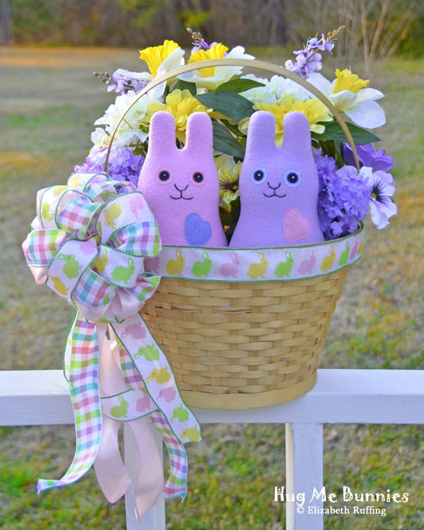 Pink and Lavender fleece Hug Me Bunny handmade stuffed animal plush toy rabbits by Elizabeth Ruffing on an Easter basket with flowers and ribbon, Ruffing's