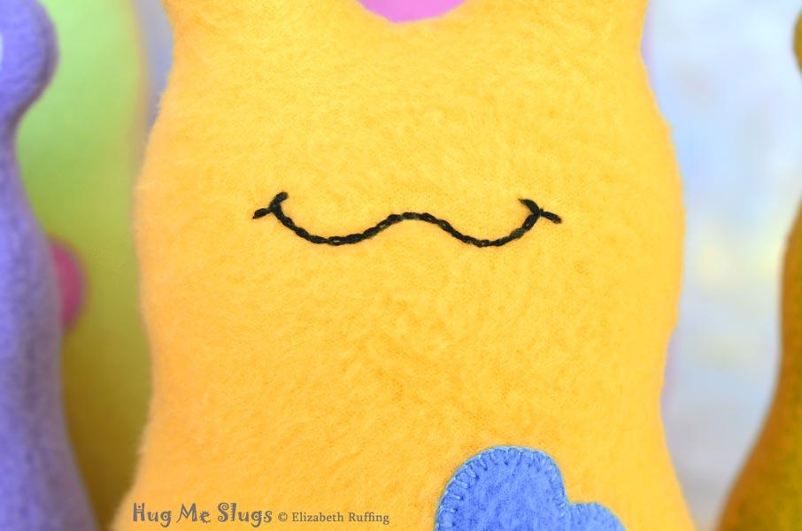 Chain Stitched Smile on Handmade Fleece Hug Me Slug Stuffed Animal Plush Art Toy by artist Elizabeth Ruffing