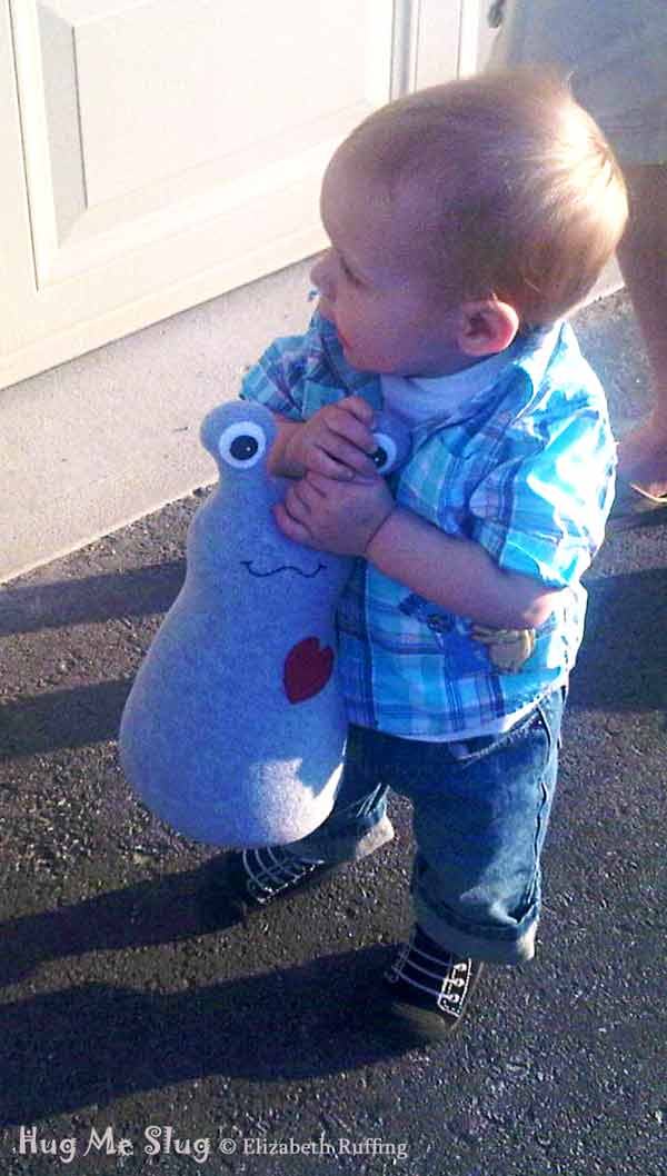 12 inch Handmade Gray Hug Me Slug Stuffed Animal Art Toy, by artist Elizabeth Ruffing, carried by a toddler