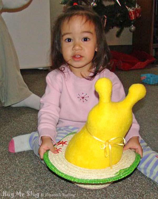 12 inch Handmade Bright Yellow Hug Me Slug Stuffed Animal Art Toy, by artist Elizabeth Ruffing, sitting in a straw hat