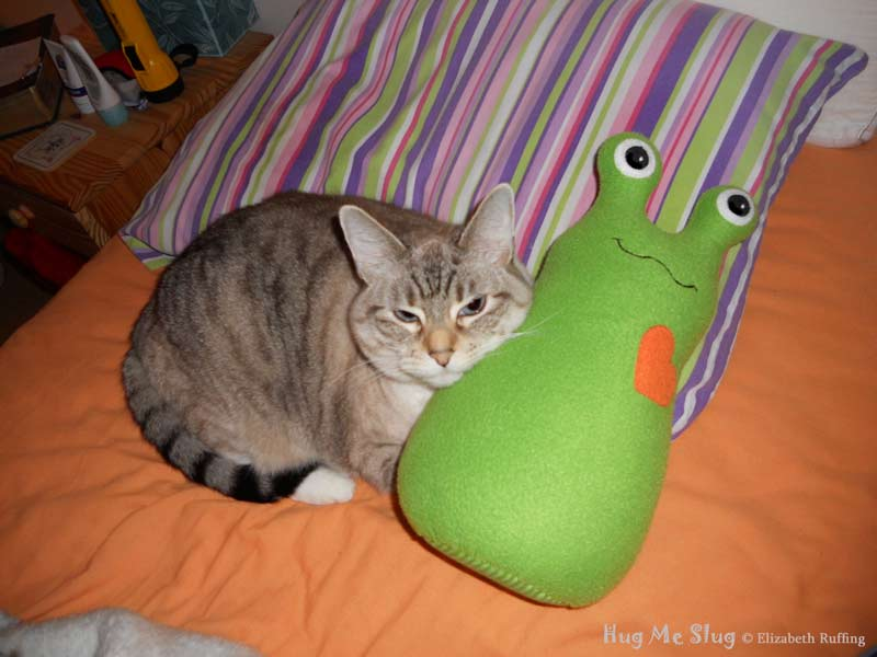 Tabby cat cuddling with a grass green Hug Me Slug stuffed animal art toy by artist Elizabeth Ruffing