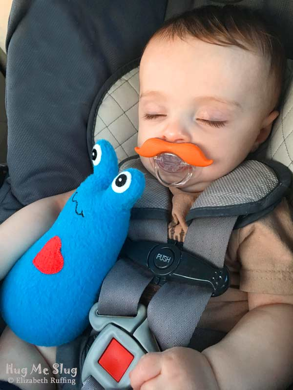 Baby napping in car seat with a 7 inch Handmade Royal Blue Hug Me Slug Stuffed Animal Art Toy, by artist Elizabeth Ruffing