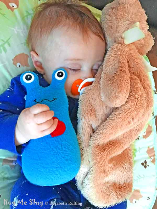 Baby sleeping with a 7 inch Handmade Royal Blue Hug Me Slug Stuffed Animal Art Toy, by artist Elizabeth Ruffing