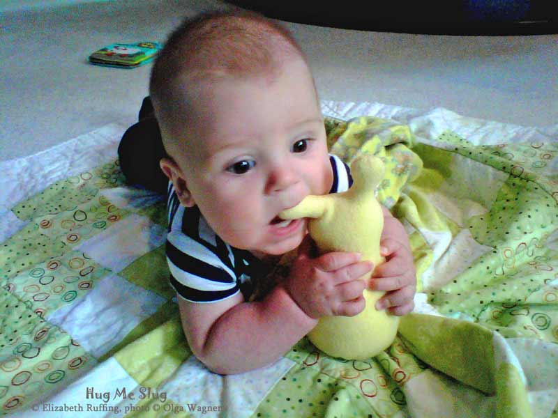 Baby with a 7 inch Handmade Hug Me Slug Stuffed Animal Plush Art Toy in his mouth, by artist Elizabeth Ruffing