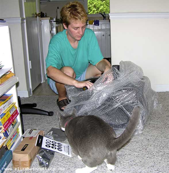 Elizabeth Ruffing unboxing an office chair with kitty assistant