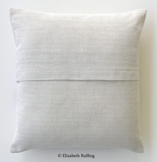 Oatmeal-colored cotton, decorative throw pillow with an envelope closure
