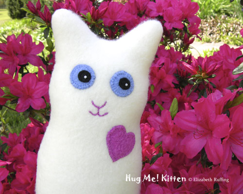 Cream-colored Fleece Hug Me Kitten by Elizabeth Ruffing in dark pink azaleas