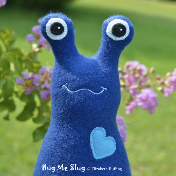 Dark royal blue fleece Hug Me Slug by Elizabeth Ruffing, with purple-pink crape myrtle