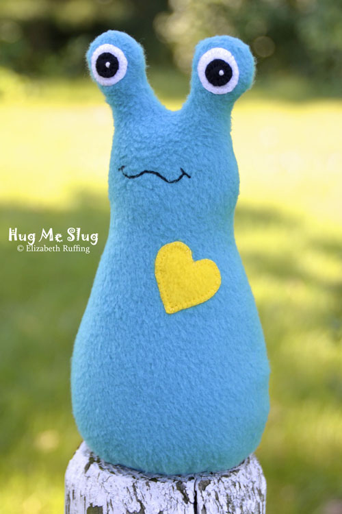 Turquoise fleece Hug Me Slug with a bright yellow heart by Elizabeth Ruffing