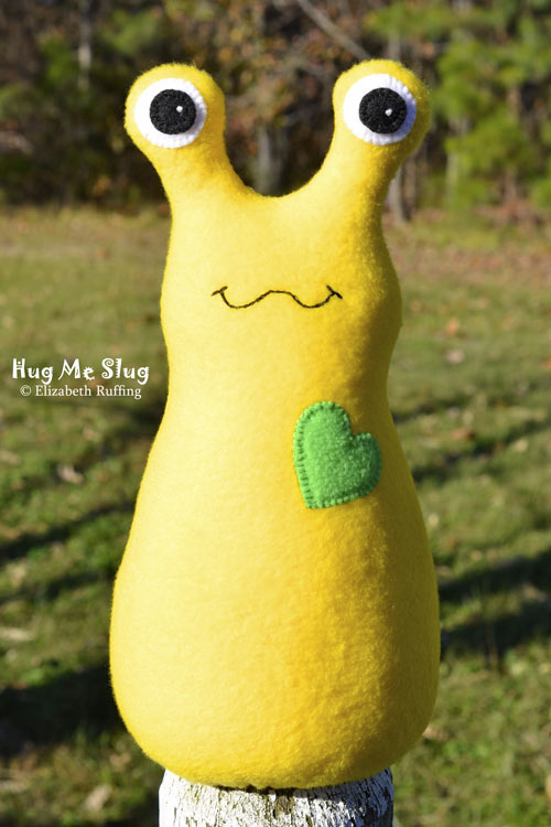 Bright yellow fleece Hug Me Slug art toy by Elizabeth Ruffing