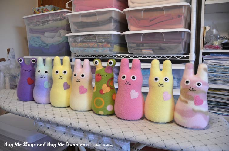 Fleece Hug Me Slugs and Hug Me Bunnies, all in a row, original art toys by Elizabeth Ruffing