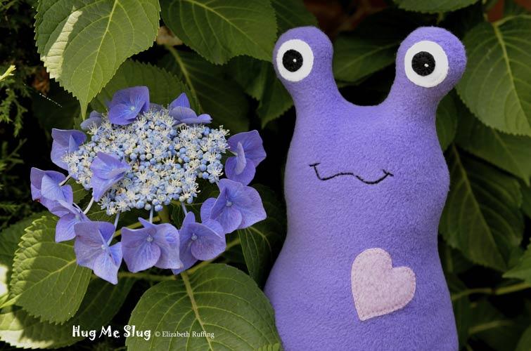 Purple Hug Me Slug with blue lace-cap hydrangea, original art toys by Elizabeth Ruffing
