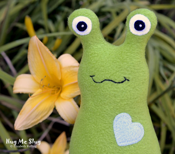 Grass green fleece Hug Me Slug, with a yellow heart and daylilies, original art toy by Elizabeth Ruffing
