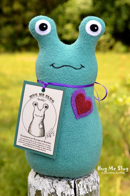 Teal fleece Hug Me Slug, with a double heart, original art toy by Elizabeth Ruffing