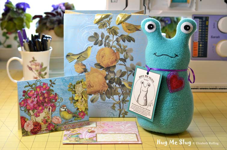 Teal fleece Hug Me Slug, with a double heart, original art toy by Elizabeth Ruffing