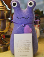 Purple fleece Hug Me Slug handmade stuffed animal art toy by artist Elizabeth Ruffing with a personalized hang tag with a poem on the back