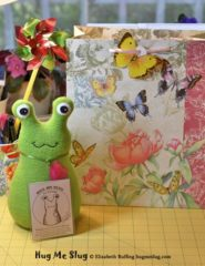 Grass green Hug Me Slug stuffed animal art toy by artist Elizabeth Ruffing with pink butterfly gift bag and personalized hang tag
