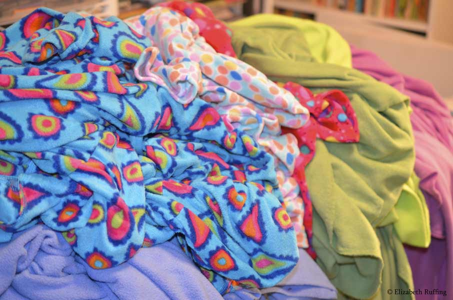 Brightly-colored piles of fleece pajamas and throws, novelty prints and solids