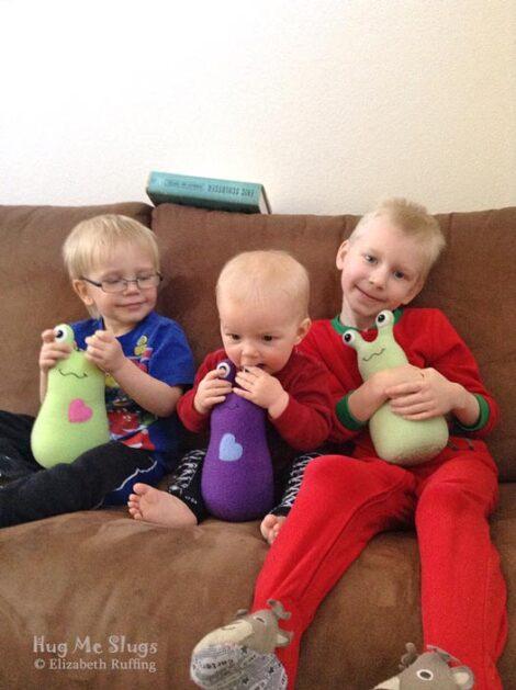 Three brothers with their pear green and purple fleece Hug Me Slug plush toys