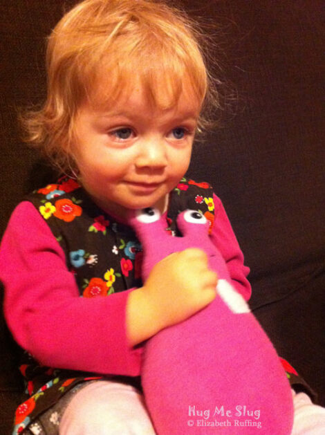 Toddler hugging her fuchsia pink fleece Hug Me Slug plush toy