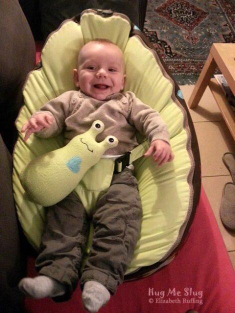 Laughing baby with a pear green fleece Hug Me Slug plush toy