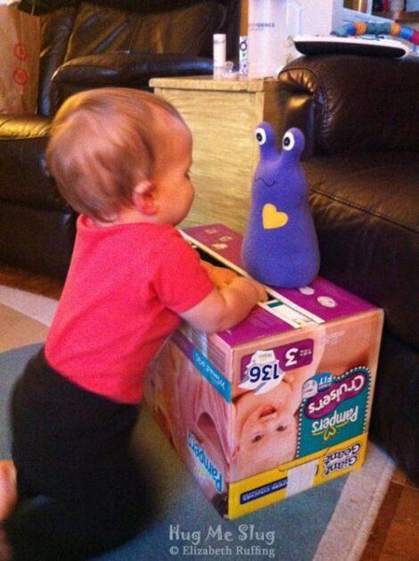 Toddler staring at a purple fleece Hug Me Slug plush toy
