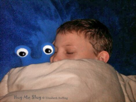 Royal blue fleece Hug Me Slug plush toy under covers with sleeping boy