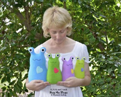 Elizabeth Ruffing holding 12, 9, 8, 7 inch fleece Hug Me Slug plush toys