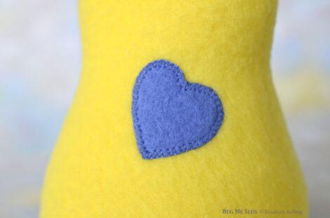 Cobalt blue hand stitched heart, Pineapple Yellow Fleece Hug Me Slug Handmade Plush Art Toy by artist Elizabeth Ruffing